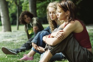 Two Young Girls Sitting on the Grass and Ignoring a Young Boy Watching Them